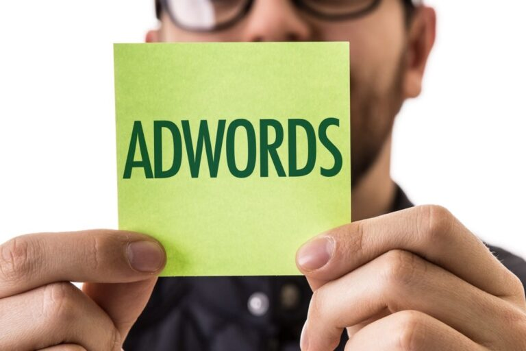 a man holding up a post it note with the word AdWords written on it