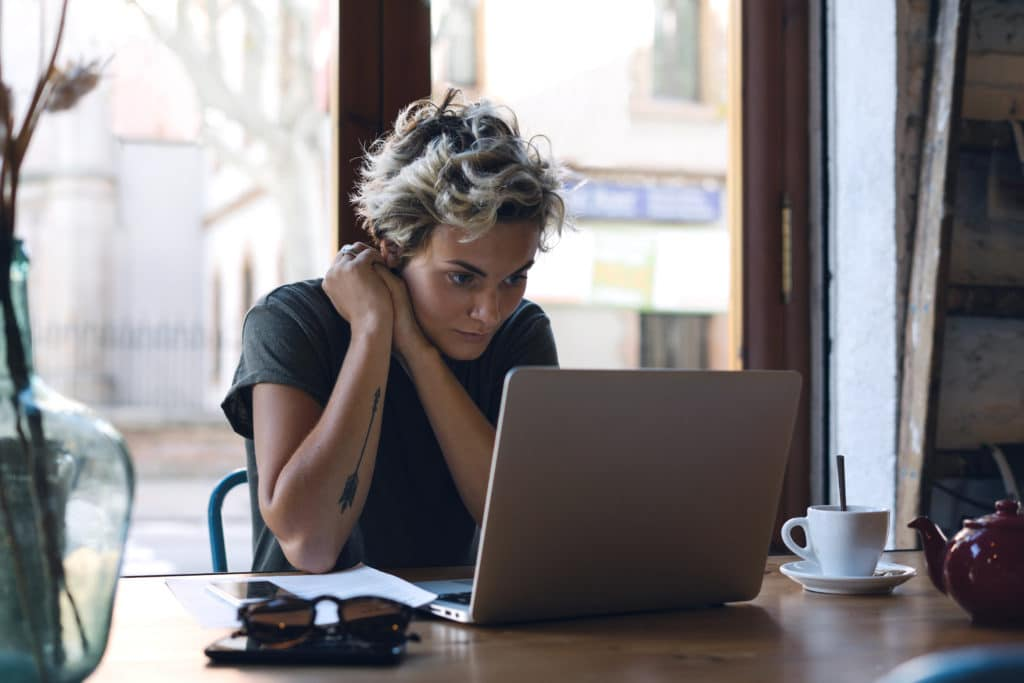 a young woman looking at her laptop at a coffee shop