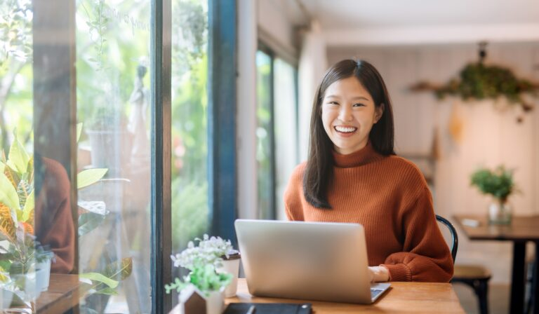 young woman on her laptop in a trendy coffee shop
