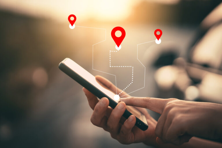 Man hand using smartphone with gps navigator map icon on blur street background. Technology lifestyle and business travel concept. Vintage filter effect color style.